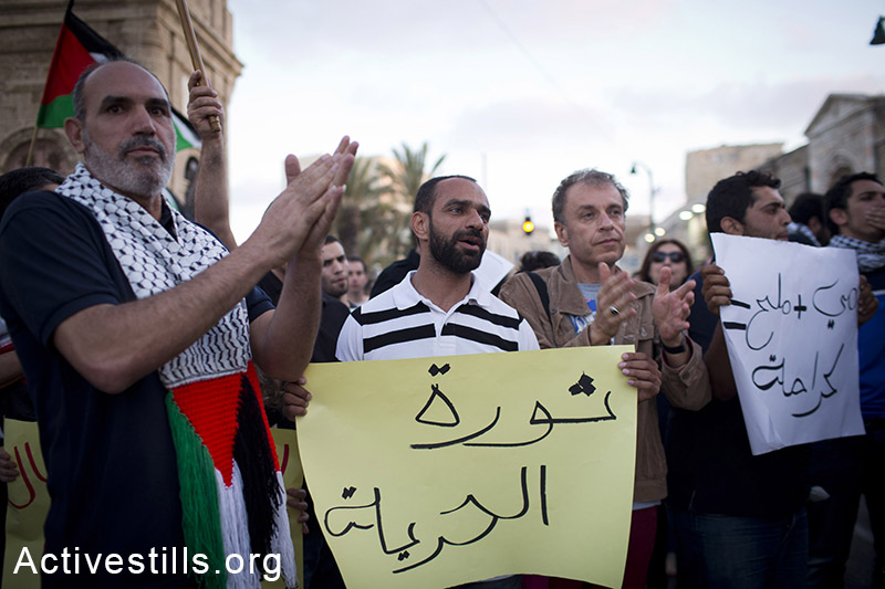 Samer Issawi holds takes part in a protest with other Palestinians activists living in Israel and Israeli activists in a solidarity with the Palestinian prisoners on hunger strike in Israeli jails, Jaffa, May 25, 2014. More than 100 Palestinian administrative prisoners in Israeli jails launched a mass, open-ended hunger strike on Thursday, April 24, 2014. A few of them are now hospitalized in Israeli medical centres due to the strike. (Oren Ziv/Activestills.org)
