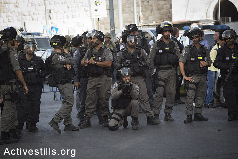 Israeli policemen shot rubber bullets to disperse Palestinians gathering to protest  against the 'flag march', in which Israeli settlers and Ultra-nationalists march through Damascus Gate in east Jerusalem, on May 28, 2014, celebrating the anniversary of its capture in the 1967 Six-Day War. Police prevented from Palestinians to gather and  protest against the march, and attacked journalists that were covering  the event. (Oren Ziv/Activestills.org)