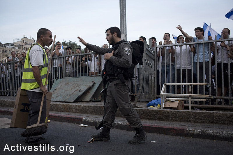 A Palestinian cleaning worker argues with Israeli settlers as during a protest against the 'flag march', in which Israeli settlers and Ultra-nationalists march through Damascus Gate in East Jerusalem, on May 28, 2014, celebrating the anniversary of its capture in the 1967 Six-Day War. Police prevented from Palestinians to gather and  protest against the march, and attacked journalists that were covering  the event. (Oren Ziv/Activestills.org)