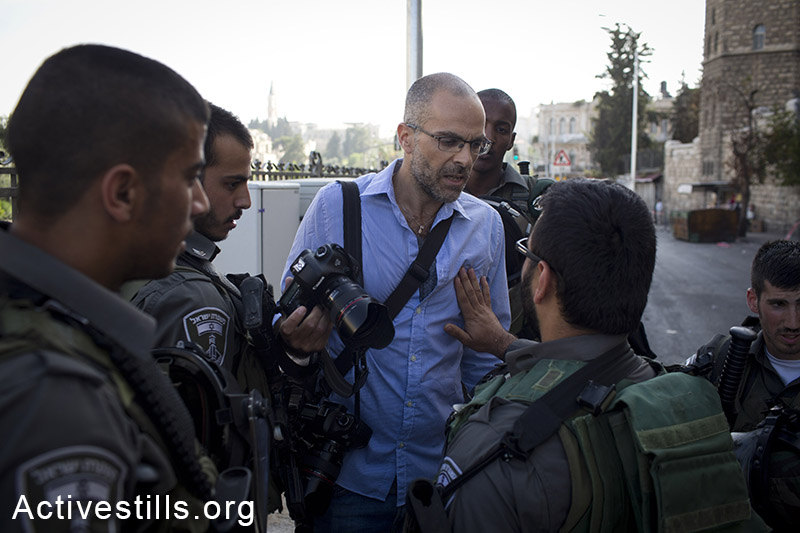 Israeli border policemen checks the ID of a photojournalist as Israeli settlers and Ultra-nationalists take part in the 'flag march' through Damascus Gate in east Jerusalem, on May 28, 2014, celebrating the anniversary of its capture in the 1967 Six-Day War. Police prevented from Palestinians to gather and  protest against the march, and attacked journalists that were covering  the event. (Oren Ziv/Activestills.org)