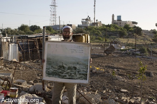 Nabi Samuel resident Eid Barakat stands in front of the mosque holding a picture of his village, destroyed by Israeli bulldozers in 1971, when Eid was seven years old. (Photo: Mareike Lauken and Keren Manor/Activestills.org)