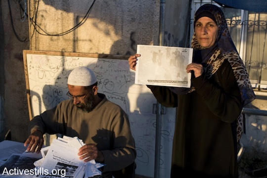Eid Barakat lays out demolition orders given to his family over the years: among them, demolition orders relating to a storage unit, a fence and olive trees. (Photo: Mareike Lauken and Keren Manor/Activestills.org)