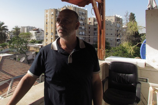 Burgal on his balcony. He speaks of his torture calmly. (photo: Rami Younis)