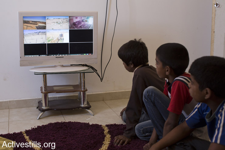 The Adisan family watches recordings from the cameras installed around their property. (photo: Keren Manor / Activestills.org)