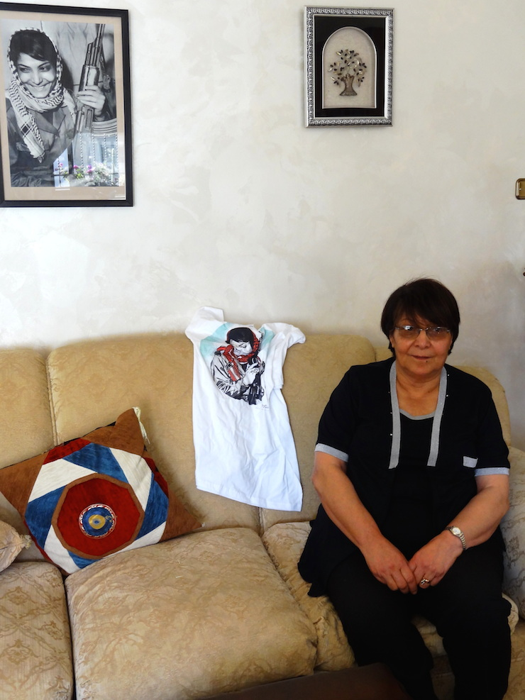Leila Khaled at her home in Amman, posing with the famous picture of her holding a Kalashnikov rifle, and a T-shirt made by Mlabbas exclusively for her. (Photo: Paula Schmitt)
