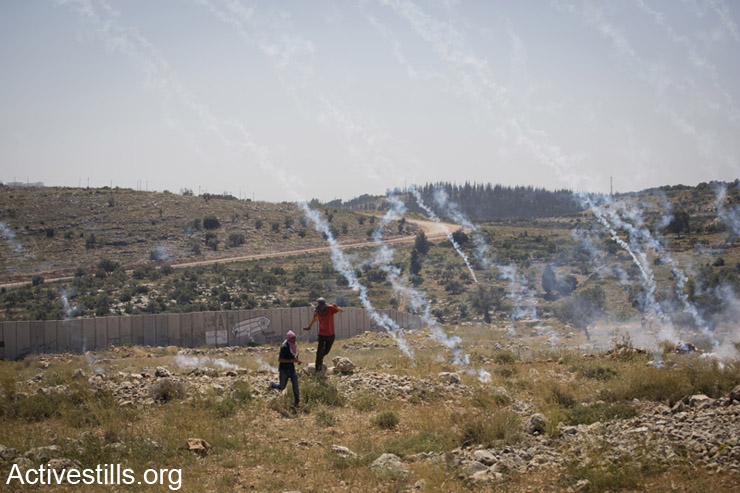 Palestinian youth run as the Israeli army shoots tear gas during a protest against the Israeli separation wall in the West Bank village of Nil'in, April 25, 2014. (Activestills.org)