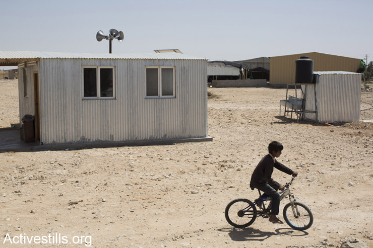 A child rides a bicycle next to a mosque in the Bedouin village of Bir-Hadaj, Negev Desert, April 27, 2014. (Activestills.org)