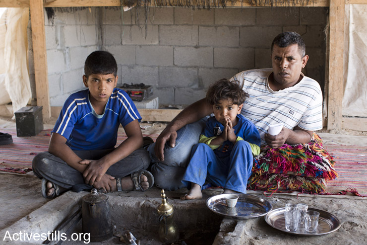 Ayad Adsan sits with two of his eight children in their family home a few hours after civil administration officers and policemen hung a demolition warning on his house in the Bedouin village of Bir-Hadaj, Negev Desert, April 27, 2014. Bir-Hadaj is a recognized Bedouin village in Israel since 1999 and its urban plan was approved in 2003. The village still lacks basic infrastructure and its inhabitants frequently face demolition orders and harsh treatment by the police. (Activestills.org)