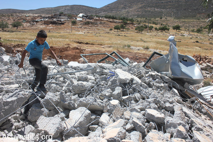A Palestinian child climbs over the rubble of a demolished mosque in Khirbet Twaiel, West Bank, April 30, 2014. (Photo: Activestills.org)