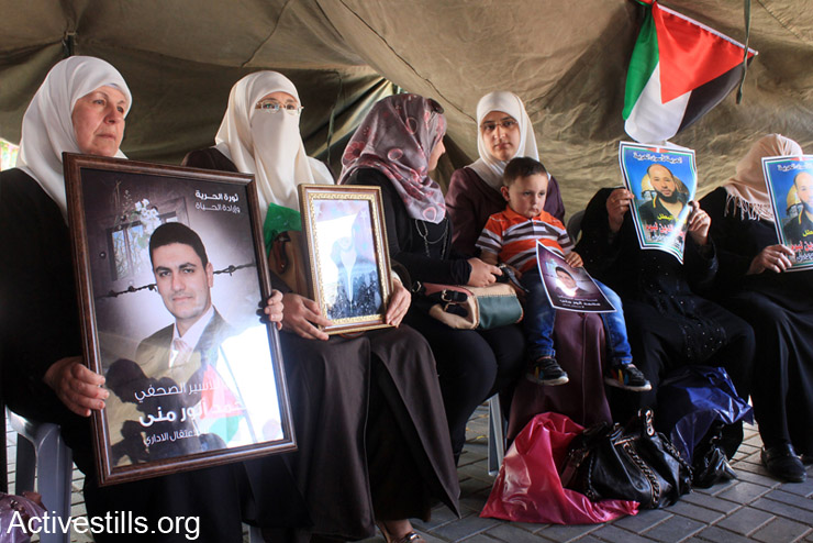 Palestinian women hold pictures of administrative prisoners in solidarity with them during the first day of a protest tent that was erected in the city center of Nablus, West Bank, April 28, 2014. More than 100 Palestinian administrative detainees in Israeli prisons launched a mass, open-ended hunger strike on Thursday, April 24, 2014. The hunger strike is taking place in the Ofer, Megiddo, and Negev prisons and comes after Israeli authorities reneged on a promise made following an earlier mass hunger strike to limit the use of administrative detention to exceptional cases. (Activestills.org)
