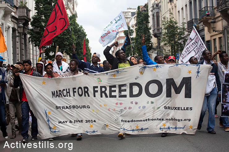 Activists carry a banner during the final day of the March for Freedom of migrants, Brussels, Belgium, June 20, 2014. The 500-kilometer protest march held by migrants, refugees, asylum seekers and supporters started in Strasbourg, France, five weeks ago and ended in Brussels for a week of action. The march across Europe demands radical changes in European asylum policy and the rights for all people to move freely. Since 2000, more than 20,000 migrants have died while attempting to reach Europe.  (Activestills.org)