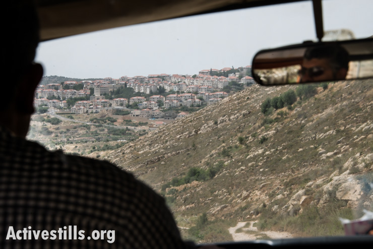 The Israeli settlement Beitar Illit covers a nearby hilltop as Daoud Nassar drives to his family farm, known as Tent of Nations, near the West Bank village of Nahalin, June 3, 2014.
