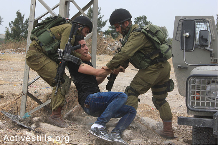 Israeli soldiers arrest a Palestinian man during the 'Return March,' held alongside the separation wall near Tulkarm, West Bank, May 31, 2014. Palestinians tried to cross the barrier while chanting for their destroyed villages and towns located inside Israel. By 1948, Zionist gangs ahd destroyed more than 500 Palestinian villages prior to the establishment of the State of Israel.