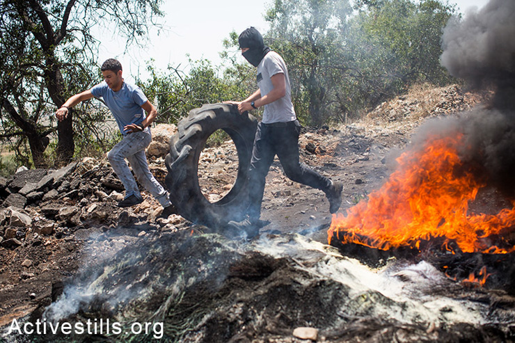 Youth roll tires during the weekly demonstration in Kafr Qaddum, a West Bank village located east of Qalqiliya, May 30, 2014. Locals began to organize demonstrations in July 2011 to protest the blocking of the main road linking Kafr Qaddum to Nablus.