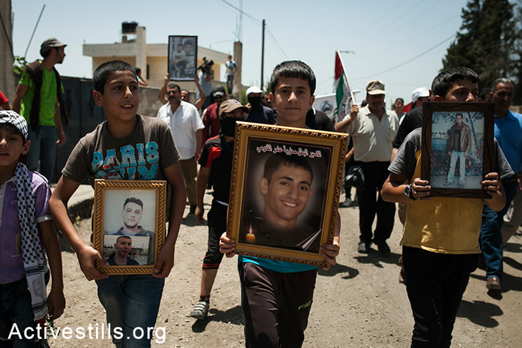 Youth holding pictures of family members arrested and imprisoned by Israeli forces during a protest against the occupation, Kfar Qaddum, West Bank, May 30, 2014. Locals began to organize demonstrations in July 2011 to protest the blocking of the main road linking Kafr Qaddum to Nablus.