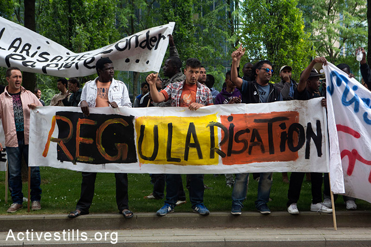 Activists carry a banner during a protest in front of the immigration office (CGRA) in Brussels, Belgium, June 25, 2014. The protest is part of a whole week of activities organized by hundreds of migrants and asylum-seekers who established a protest camp in a park in the center of Brussels. (Activestills.org)