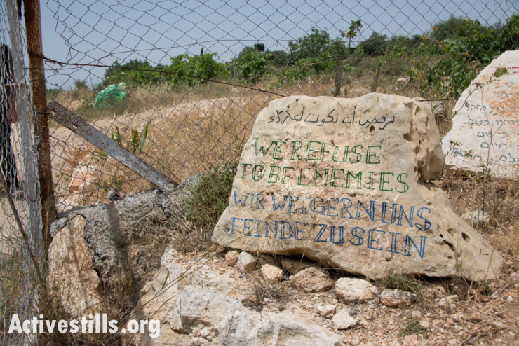 "A sign reading ""We refuse to be enemies"" marks the entrance of the Nassar family farm, known as Tent of Nations, near the West Bank village of Nahalin, June 3, 2014."