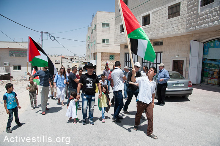 Palestinan, Israeli, and international activists march during the weekly demonstration against the Israeli separation barrier in the West Bank village of Al Ma'sara, May 30, 2014. If constructed as planned, the separation barrier would cut off the village from its agricultural lands.