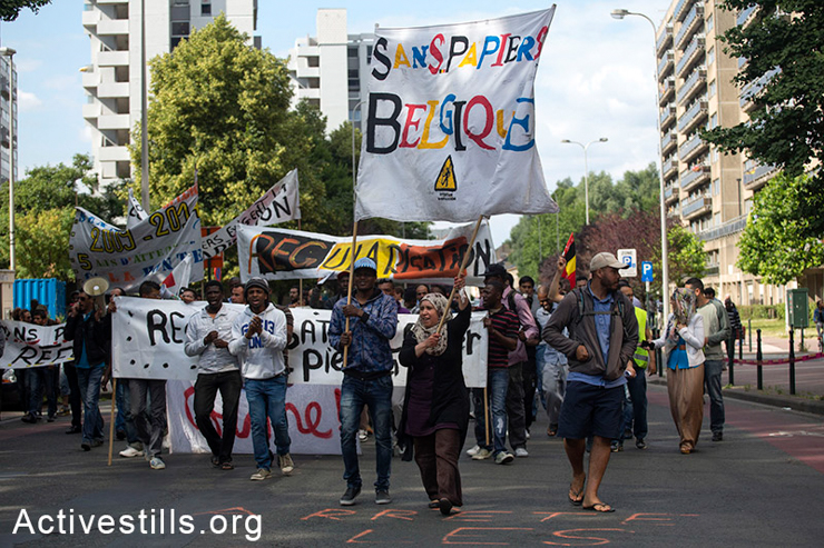 Activists carry banners during a protest in front of the immigration office (CGRA) in Brussels, Belgium, June 25, 2014. The transnational movement aims to denounce the restrictive European migration policies. The demands include permanent documents for all, freedom of movement and residency for asylum seekers, end of imprisonment and deportation. (Activestills.org)