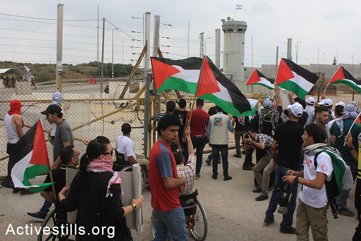 "Palestinians participate in the 'Return March"" alongside the separation wall near Tulkarm, West Bank, May 31, 2014. Palestinians tried to cross the barrier while chanting for their destroyed villages and towns located inside Israel. By 1948, Zionist gangs ahd destroyed more than 500 Palestinian villages prior to the establishment of the State of Israel."