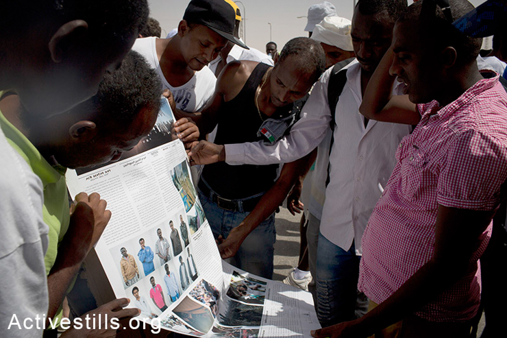 African asylum seekers jailed in the Holot detention center look at a street newspaper produced by the Activestills collective during a protest marking the International Refugee Day, June 20, 2014. (Activestills.org)