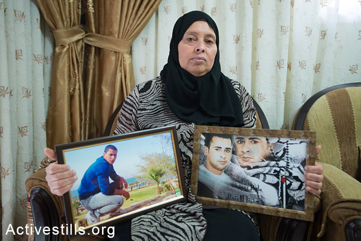 Ibtisam El Amir holds portraits of her sons Mohammad (left, age 24), who was arrested in the early morning hours of June 2, 2014, and Samir (right, age 30) who has served 11 years of a 19-year sentence in Israeli prison. Aida Refugee Camp, Bethlehem, West Bank.