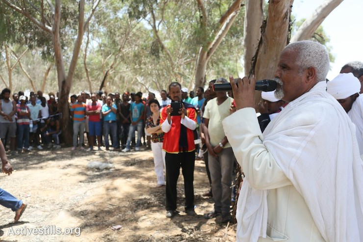 Some 200 Eritrean asylum seekers participate in a prayer session organized by clergy from the Eritrean community who arrived in a solidarity visit from Tel Aviv, June 28, 2014. More than 800 Asylum seekers walked out of the Holot open detention facility and tried to reach the border fence with Egypt, saying Israeli does not check their asylum requests and therefore they are asking for intervention from the UN and Red Cross as well as resettlement in third countries. (Photo by Oren Ziv/Activestills.org)