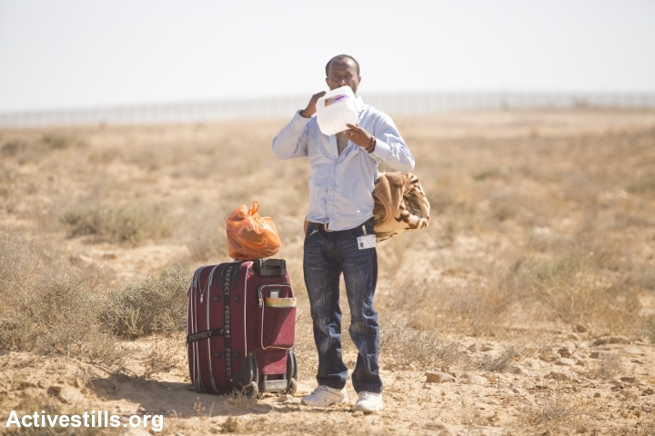 An African asylum seeker rests during a march from the Holot detention center, in which they are jailed, to the Israeli-Egyptian border in protest of Israel's asylum policies, calling on the UN and the Red Cross to intervene, Negev, June 27, 2014. More than 800 Asylum seekers tried to reach to the border fence with Egypt, saying Israeli does not check their asylum requests and therefore they are asking to be resettled in third countries. The group was stopped by the Israeli army and spent the night in a small forest located a few hundred meters from the border. (Photo by Yotam Ronen/Activestills.org)