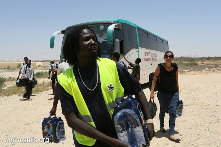 Asylum seekers and activists from Tel Aviv arrive with water and supplies to a makeshift camp where over 800 asylum seekers spent the night, June 28, 2014. More than 800 Asylum seekers walked out of the Holot open detention facility and tried to reach the border fence with Egypt, saying Israeli does not check their asylum requests and therefore they are asking for intervention from the UN and Red Cross as well as resettlement in third countries. (Photo by Oren Ziv/Activestills.org)