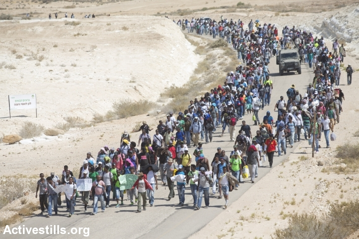 African asylum seekers march from the Holot detention center, in which they are jailed, to the Israeli-Egyptian border in protest of Israel's asylum policies, calling on the UN and the Red Cross to intervene, Negev, June 27, 2014. More than 800 Asylum seekers tried to reach to the border fence with Egypt, saying Israeli does not check their asylum requests and therefore they are asking to be resettled in third countries. The group was stopped by the Israeli army and spent the night in a small forest located a few hundred meters from the border. (Photo by Yotam Ronen/Activestills.org)