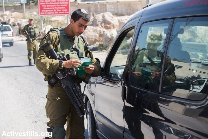 An Israeli soldier checks a Palestinian man's documents at a checkpoint outside the West Bank city of Hebron on June 17, 2014, as the hunt for three Israeli teenagers believed kidnapped by militants entered its fifth day. (Photo: Tess Scheflan/Activestills.org)