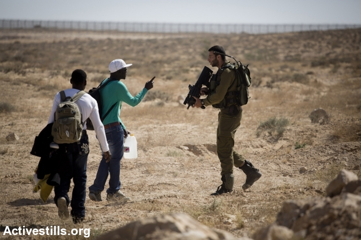 An Israeli soldier tries to stop African asylum seekers as they march from the Holot detention center, in which they are jailed, to the Israeli-Egyptian border in protest of Israel's asylum policies, calling on the UN and the Red Cross to intervene, Negev, June 27, 2014. More than 800 Asylum seekers tried to reach to the border fence with Egypt, saying Israeli does not check their asylum requests and therefore they are asking to be resettled in third countries. The group was stopped by the Israeli army and spent the night in a small forest located a few hundred meters from the border. (Photo by Oren Ziv/Activestills.org)