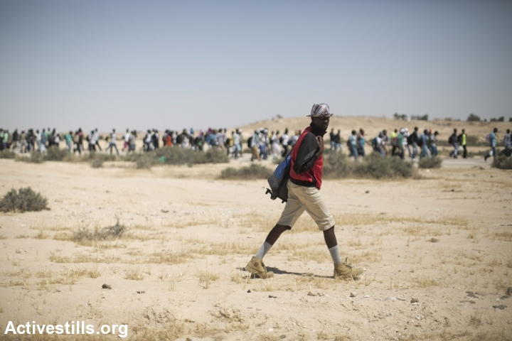 African asylum seekers march from the Holot detention center, in which they are jailed, to the Israeli-Egyptian border in protest of Israel's asylum policies, calling on the UN and the Red Cross to intervene, Negev, June 27, 2014. More than 800 Asylum seekers tried to reach to the border fence with Egypt, saying Israeli does not check their asylum requests and therefore they are asking to be resettled in third countries. The group was stopped by the Israeli army and spent the night in a small forest located a few hundred meters from the border. (Photo by Oren Ziv/Activestills.org)