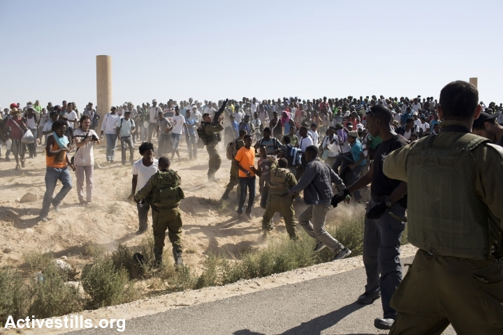 Israeli soldiers try to stop African asylum seekers as they march from the Holot detention center, in which they are jailed, to the Israeli-Egyptian border in protest of Israel's asylum policies, calling on the UN and the Red Cross to intervene, Negev, June 27, 2014. More than 800 Asylum seekers tried to reach to the border fence with Egypt, saying Israeli does not check their asylum requests and therefore they are asking to be resettled in third countries. The group was stopped by the Israeli army and spent the night in a small forest located a few hundred meters from the border. (Photo by Oren Ziv/Activestills.org)
