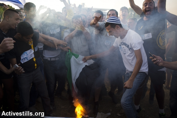 Right-wing Israeli settlers burn a Palestinian flag and shout racist slogans during an anti-Palestinian demonstration at [Gush] Etzion junction, a bloc of settlements next to the Palestinian city of Bethlehem, June 16, 2014. Three Israeli teenagers were kidnapped near the Etzion junction late last week. (Oren Ziv/Activestlls.org)