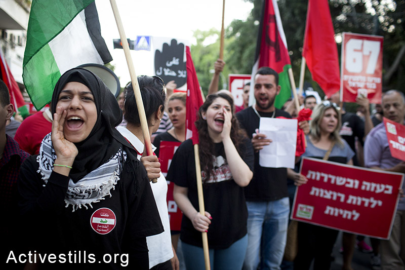 Palestinians citizens of Israel and Israeli activists participate in a protest march in Tel Aviv marking 47 years since Israel's occupation of the West Bank and Gaza, June 7, 2014. (Oren Ziv/Activestills.org)