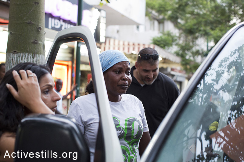 Maryam Aharon, a Sudanese asylum seeker from Darfur, talking with immigration police officers after her restaurant was raided by city inspectors, Tel Aviv, June 11, 2014. The inspectors threw food into the garbage, claiming the business is unhygienic. This action is part of the general pressure by the authorities on the asylum seeker community. (Keren Manor/Activestills.org)