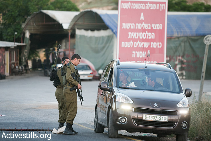 Israeli soldiers stop Palestinians at a flying check-point at the entrance to the West Bank city of Hebron, June 15, 2014. (Yotam Ronen/Activestills.org)