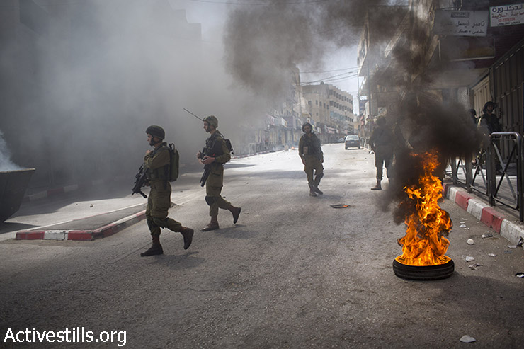 Israeli soldiers walk during clashes in the West Bank city of Hebron, after the Israeli army raided the city in the last days, June 16, 2014. (Oren Ziv/Activestills.org)