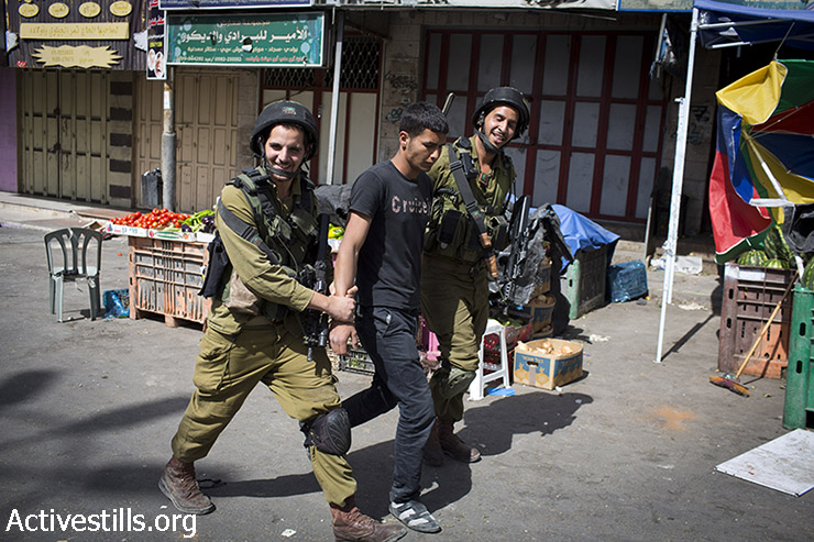 Israeli soldiers arrest a Palestinian youth during clashes in the West Bank city of Hebron, after the Israeli army raided the city in the last days, June 16, 2014. (Oren Ziv/Activestills.org)