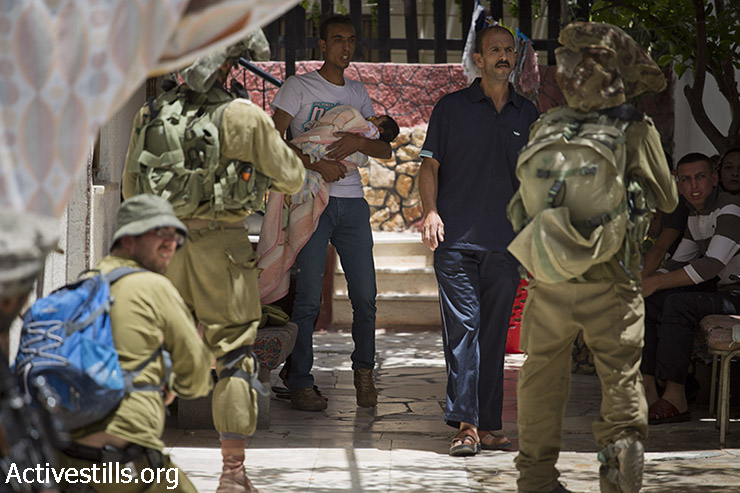 Israeli soldiers raid a house of a Palestinian family  in the West Bank town of Halhul, June 16, 2014. (Oren Ziv/Activestills.org)