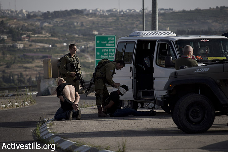 Israeli soldiers detain Palestinian men at the Gush Etzion junction, a settlement next to the Palestinian town of Bethlehem ,on June 16, 2014 , June 16, 2014.  Over 150 Palestinians were arrested in the last nights and a tight closure was imposed on the southern West Bank city of Hebron. (Oren Ziv/Activestills.org)