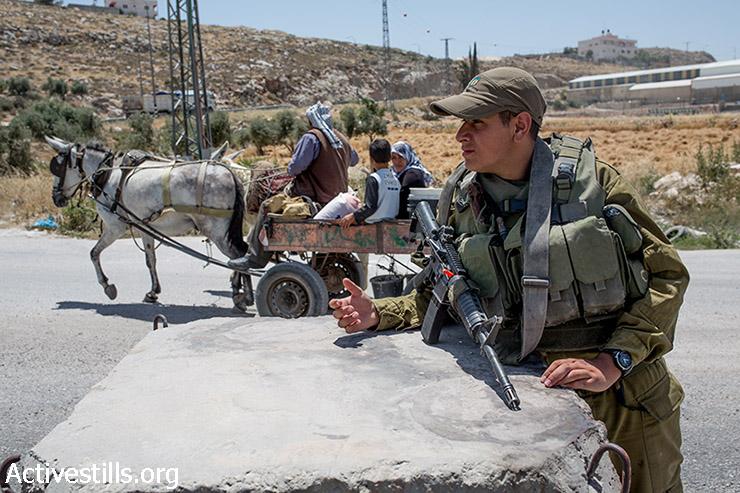 Israeli soldiers stand next to a roadblock near Hebron  on June 17, 2014. (Yotam Ronen/Activestills.org)