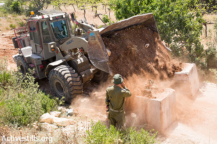 Israeli soldiers stand next to an army bulldozer blocking an entrance to the city of Hebron, June 17, 2014. (Yotam Ronen/Activestills.org)