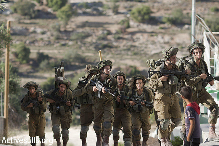 Israeli soldiers in the fifth day of the search operation walking in the West Bank city of Hebron, June 17, 2014. (Mustafa Bader/Activestills.org)