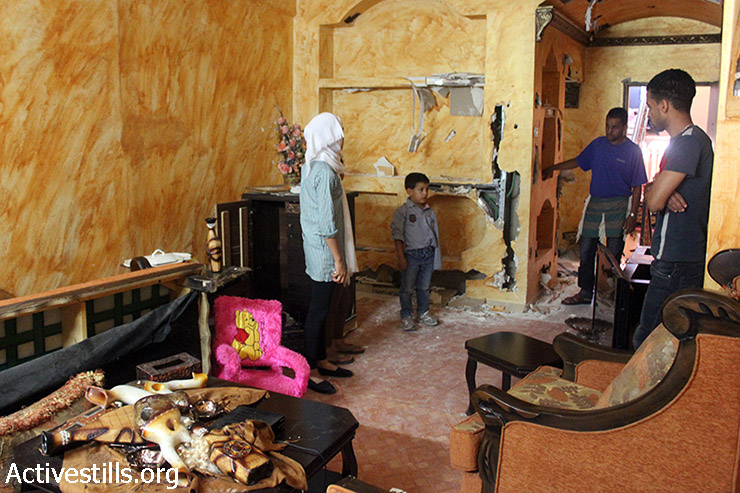 Palestinian members of Al-Naji family check the damage of their house after Israeli army raided it at the early morning of June 16, in Balata refugee camp near the West Bank city of Nablus, June 16, 2014. (Ahmad Al-Bazz/Activestills.org)