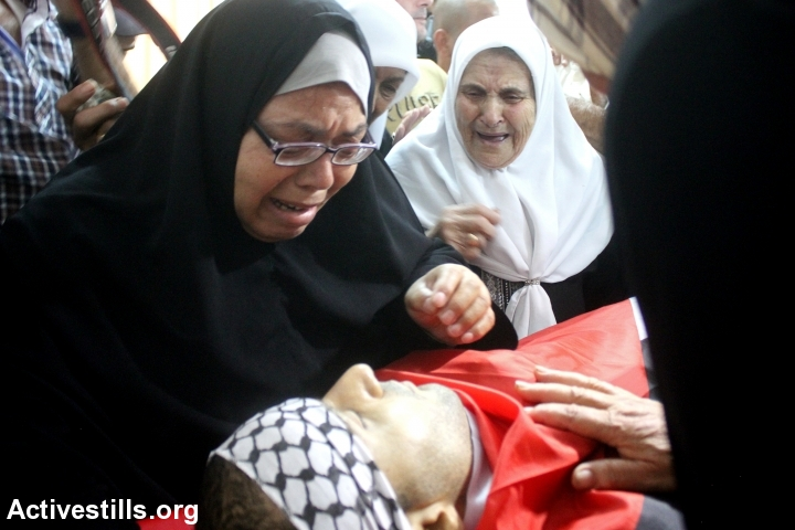 Relatives grieve over the body of 26-year-old Ahmed Fahmawi, who was killed by Israeli soldiers at Al Ein Refugee Camp during a night raid, Nablus, West Bank, June 22, 2014. According to Palestinian medical sources, Israeli soldiers killed Fahmawi near his home after they raided the refugee camp in search of three Israeli settlers. (Activestills.org)