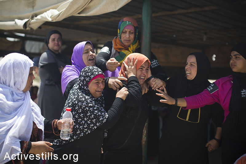 Residents of the Bedouin village of Al-Arakib react as Israeli authorities destroy the village for the 65th time, June 12, 2014. The Israeli Land Administration (ILA), backed by large police forces, entered the village in the early hours of the morning and destroyed every structure, including the mosque. (Oren Ziv/Activestills.org)