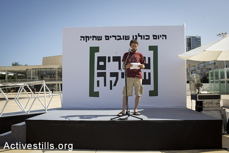 An Israeli activist reads testimonies during a gathering held in the city of Tel Aviv to mark the 10th anniversary of the Israeli NGO Breaking the Silence, and 47 years since the beginning of the Israeli occupation of the Palestinian territories, June 6, 2014. Breaking the Silence was founded by former Israeli army soldiers who seek to expose the reality of the military occupation of the Palestinian territories. (Oren Ziv/Activestills.org)