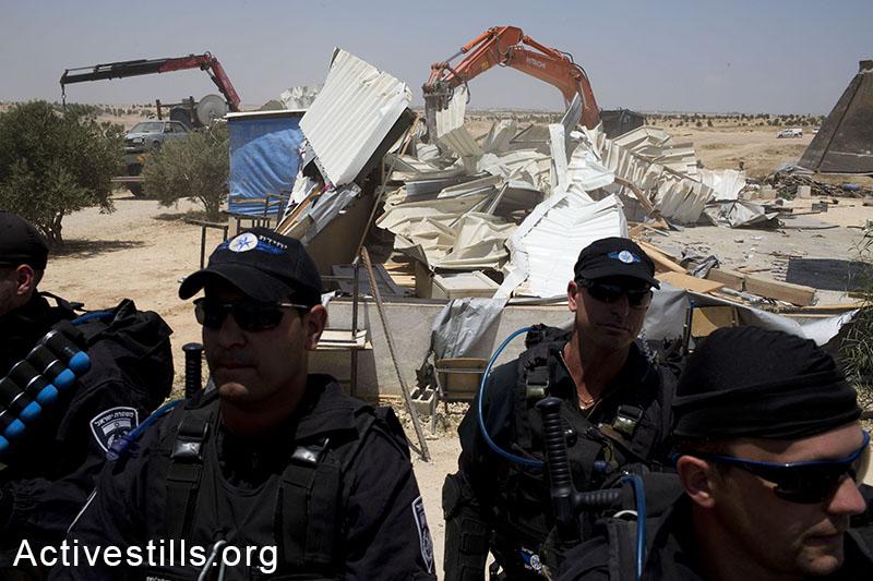 Israeli policemen guard as bulldozers destroy Al-Arakib for the 65th time, June 12, 2014. (Oren Ziv/Activestills.org)